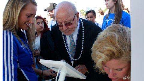 Bobby Campbell looking at an iPad at the Bobby Campell Stadium dedication event