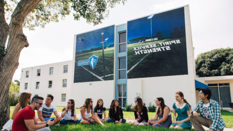 Students sitting in the lawn next to an athletics building wrap.