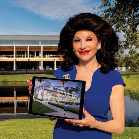 Christine E. Lynn holding iPad in front of the University Center in progress