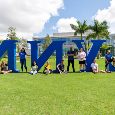 Students in front of the 林恩 letters on the grass.