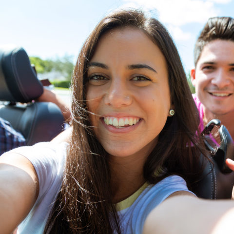 Two students taking a selfie while riding in the passengers seat.