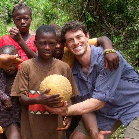 Student poses with some children during the Study abroad program