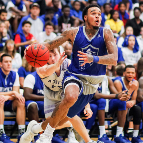 A Lynn basketball player dribbled a basketball in front of a cheering crowd.
